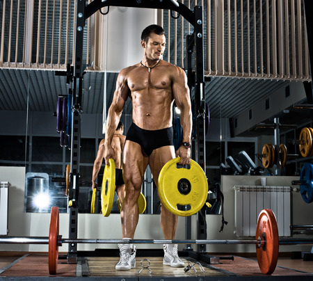 very brawny guy bodybuilder,  execute exercise with  weight photo