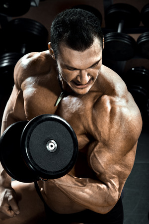 musculation: vertical close up portrait handsome guy bodybuilder ,  execute exercise with  dumbbells, in dark gym