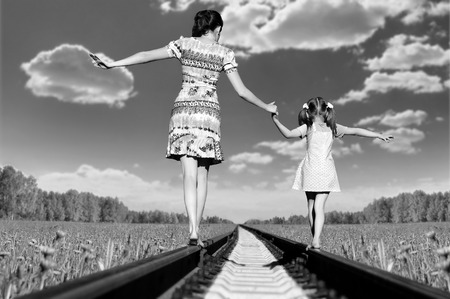 dangerously: Mother with the daughter go on rails, a back to a camera, in field, in the summer