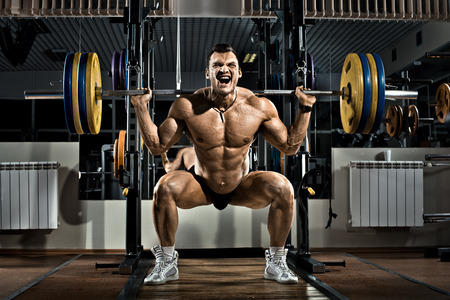 bodybuilder man: very brawny guy bodybuilder ,  execute exercise squatting with weight, in gym Stock Photo