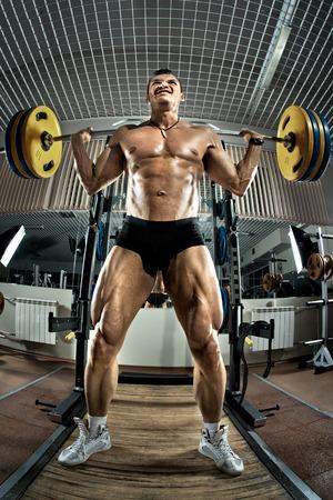 en cuclillas: culturista tipo muy musculoso, ejecutar ejercicio en cuclillas con peso, en el gimnasio
