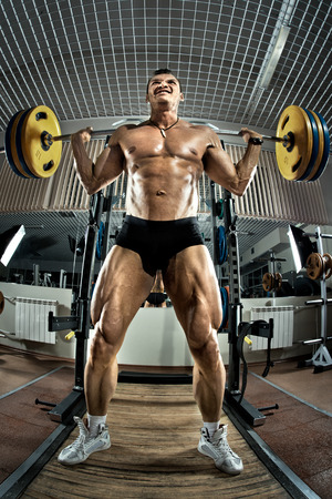 brawny: very brawny guy bodybuilder ,  execute exercise squatting with weight, in gym Stock Photo