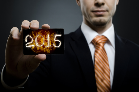 businessman in black costume and orange necktie reach out on camera and show credit card with date 2015, close up photo