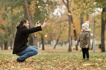happy father toss up little child with air-balloons, outing in autumn park photo
