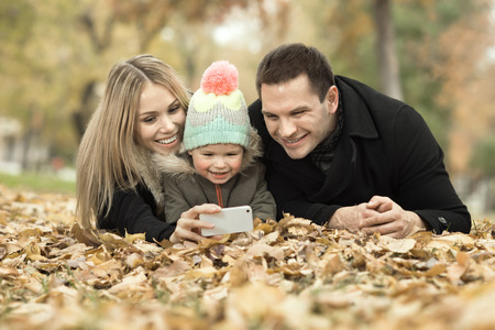 merrymaking: happy family with little child take Selfie on telephone, outing in autumn park