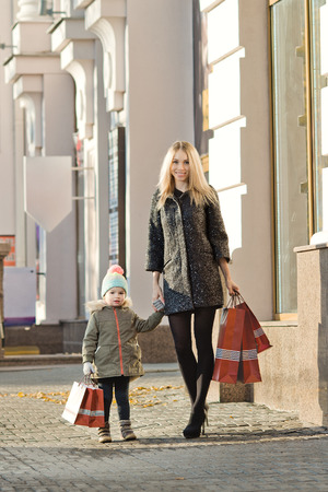 happy woman and little child with red shopping bag, walking on street photo