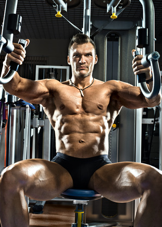 musculation: very brawny guy bodybuilder execute exercise  on gym apparatus Butterfly Machine Stock Photo