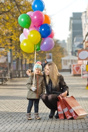 happy woman and little child with red shopping bag and air-balloons photo
