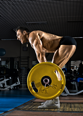 very brawny guy bodybuilder ,  execute exercise deadlift with weight, in gym