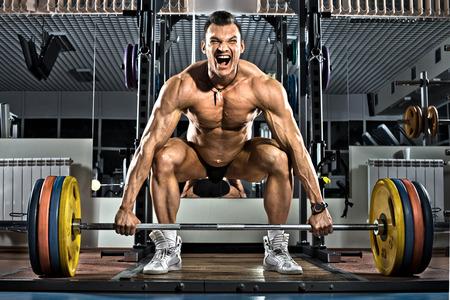 hombre fuerte: culturista tipo muy musculoso, ejecutar el ejercicio con peso muerto de peso, en el gimnasio Foto de archivo