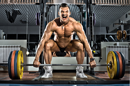 very brawny guy bodybuilder ,  execute exercise deadlift with weight, in gym photo
