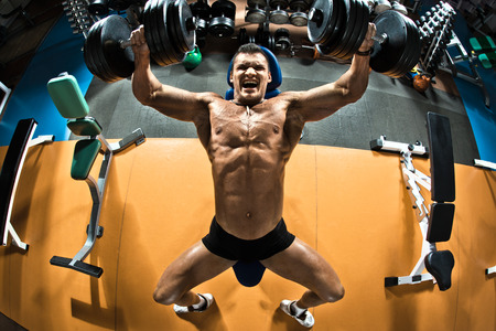 pectoral muscle: very power athletic guy bodybuilder ,  execute exercise press of dumbbells on pectoral muscle, in gym