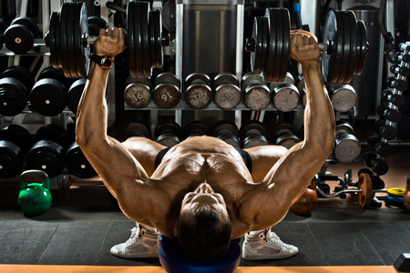 very brawny guy bodybuilder ,  execute exercise press of dumbbells on pectoral muscle, in gym