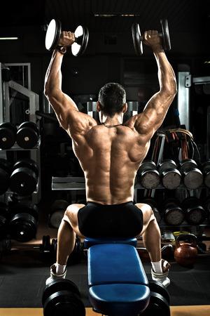 culturista: culturista tipo muy musculoso, ejecutar el ejercicio con pesas, el músculo deltoides del hombro