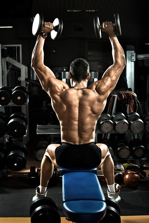 tough man: very brawny guy bodybuilder,  execute exercise with  dumbbells, on deltoid muscle shoulder Stock Photo