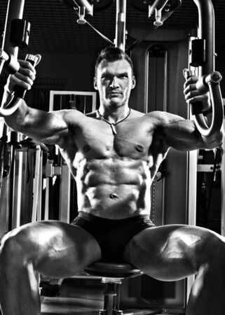 brawny: very brawny guy bodybuilder ,  execute exercise  on gym apparatus Butterfly Machine, in gym. Black-and-white photo Stock Photo
