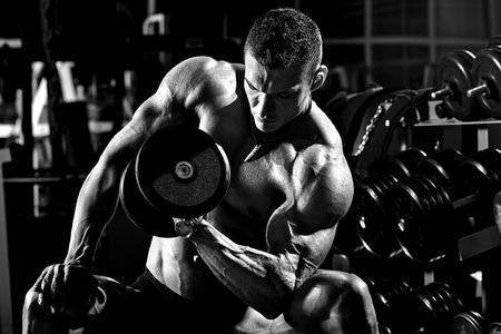 gym: very power athletic guy bodybuilder ,  execute exercise with  dumbbells, in dark gym, black and white photo