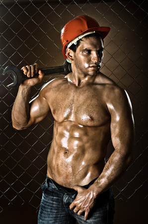 brawny: the beauty muscular worker  man, in  safety helmet  with big wrench  in hands, on netting fence background