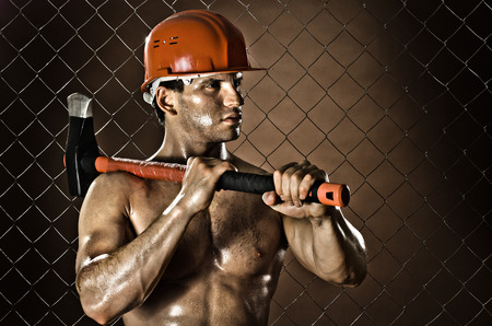 miry: the muscular  tired worker chopper man, in  safety helmet  with big  heavy ax  in hands, on netting fence background