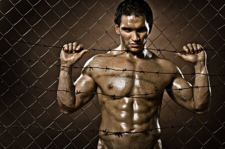 the very muscular handsome felon guy ,  out of netting   steel fence Stock Photo