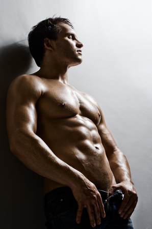 bronzed: the very muscular handsome sexy guy on   grey wall  background