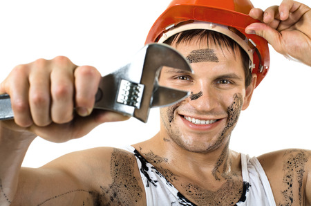 erector: happy worker man, dirty in  safety helmet  with big wrench  in hands, turn on and smile, on white background, isolated