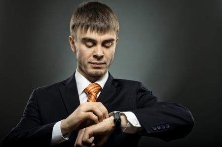 exactness: young businessman in black costume wind clock (wristwatch) on hand, closeup