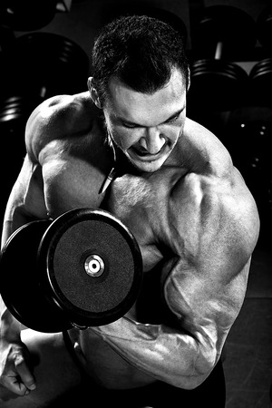musculation: vertical close up portrait handsome guy bodybuilder ,  execute exercise with  dumbbells, in dark gym, balck and white photo