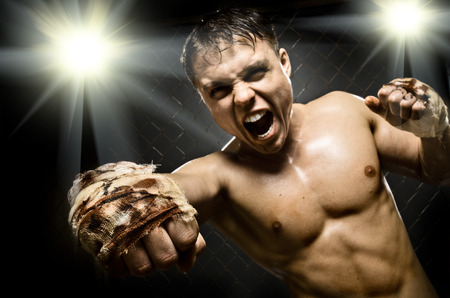 horizontal  photo  muscular young  guy street-fighter, cuff  fist close up on camera and yell , hard light photo