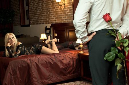 amantes en la cama: fecha velada romántica en la habitación de hotel, chico con chica sexy en la cama