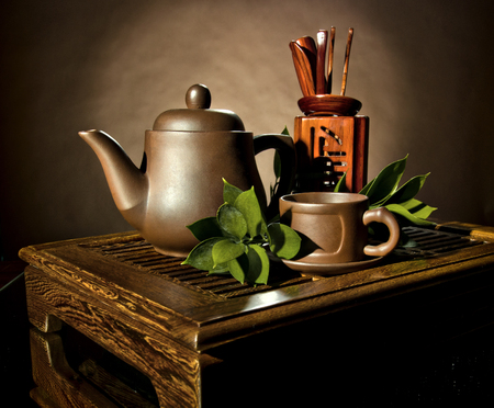 horizontal photo, still life of the clay teapot and  cup on brown background
