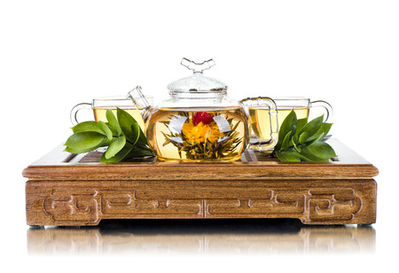 pellucid: still life of the glass teapot flow green tea in cup on wooden trivet, white background, isolated,  tea ceremony