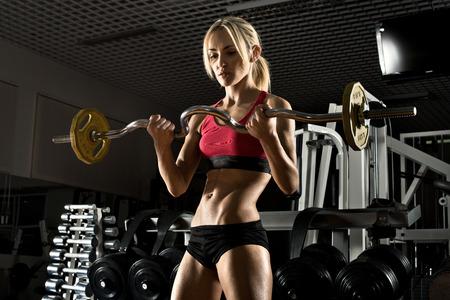 vigorous: beautiful girl bodybuilder ,  execute exercise with  weight, in dark gym