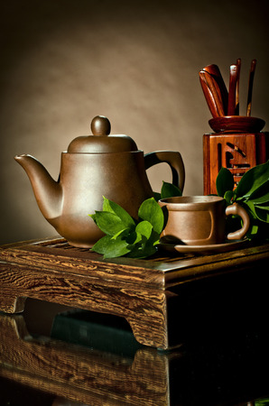 loam: vertical photo, still life of the clay teapot and  cup on brown background Stock Photo