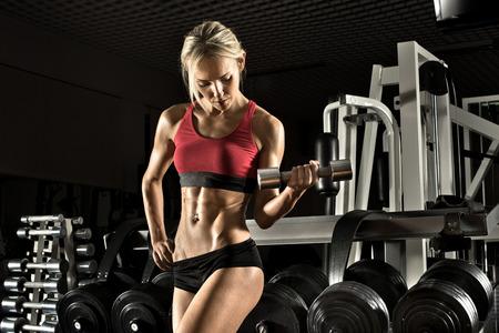 vigorously: Beautiful girl bodybuilder ,  execute exercise with  dumbbells, in dark gym