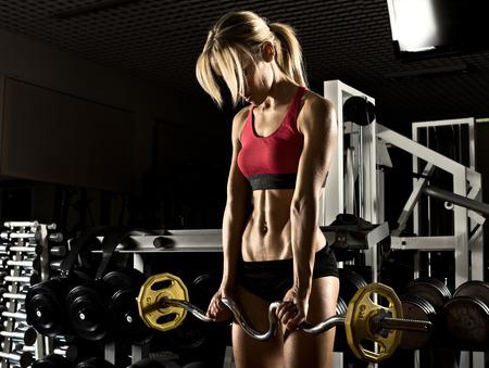 gimnasio: Culturista Hermosa niña, ejecutar el ejercicio con peso, en el gimnasio oscuro Foto de archivo