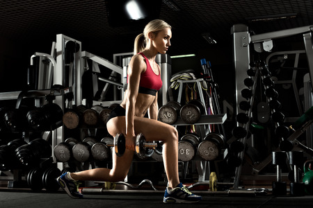 Beautiful girl bodybuilder ,  execute exercise with  dumbbells, in dark gym Reklamní fotografie - 39292541