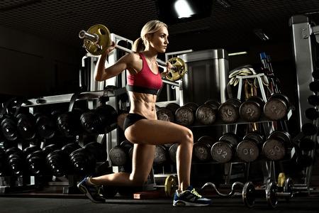 en cuclillas: Culturista Hermosa niña, ejecutar ejercicios con pesas, en el gimnasio oscuro