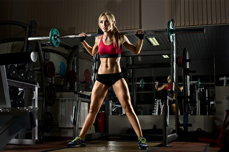 beautiful girl bodybuilder ,  execute exercise with  weight, in dark gym