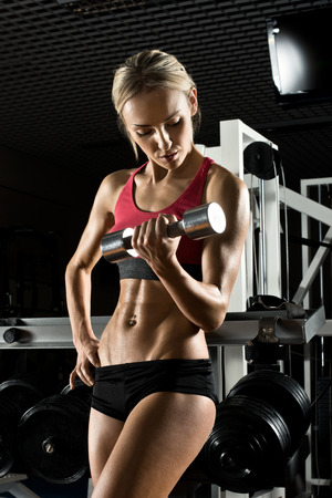 beautiful girl bodybuilder ,  execute exercise with  dumbbells, in dark gym photo
