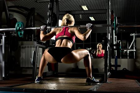 en cuclillas: hermosa chica culturista, ejecutar el ejercicio con peso, en el gimnasio oscuro