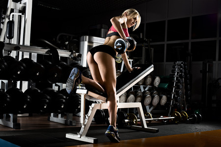 fitness girl  execute exercise with  dumbbells, on broadest muscle of back photo