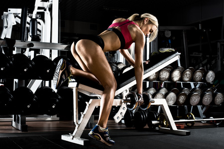 muscle people: fitness girl  execute exercise with  dumbbells, on broadest muscle of back