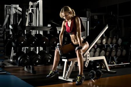 muskeltraining: ermüdet schönes Mädchen Bodybuilder, Ruhe nach dem Training mit Gewicht