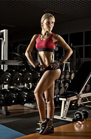 musculation: beautiful fitness girl bodybuilder,  in dark gym
