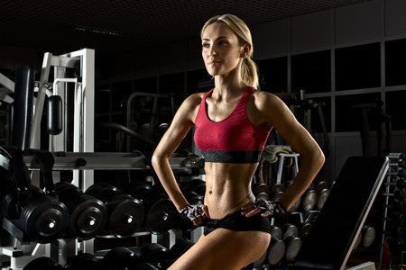 woman muscle: beautiful fitness girl bodybuilder,  in dark gym