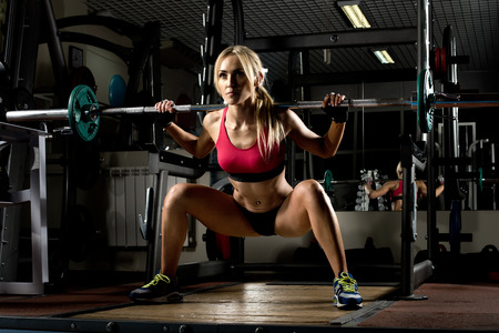 tough woman: beautiful girl bodybuilder ,  execute exercise with  weight, in dark gym