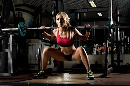 squatting: hermosa chica culturista, ejecutar el ejercicio con peso, en el gimnasio oscuro