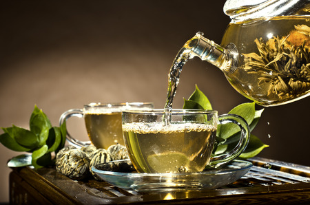 pellucid: horizontal photo, of the glass teapot flow green tea in cup on brown background,  tea ceremony