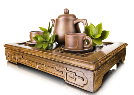 trivet: still life of the clay teapot and  cup on wooden trivet,  on white background, isolated